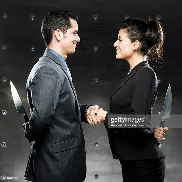 two business people with knives behind their backs