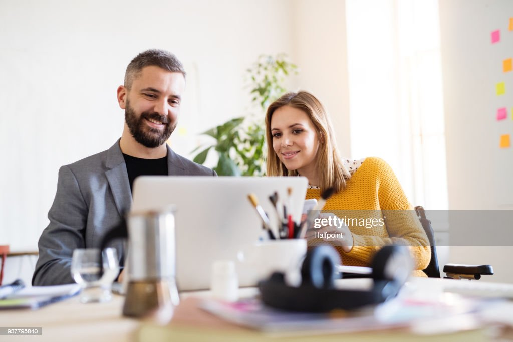 Zwei Geschäftsleute mit Rollstuhl im Büro. : Stock-Foto