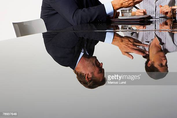 Two business people's reflection in a table.