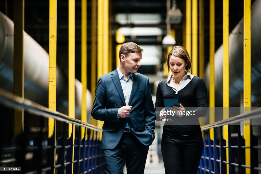 Two Business Person Walking A Dark Factory Hallway : Stock Photo