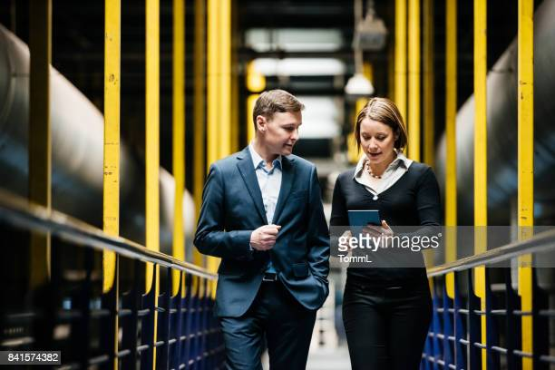 two business person walking a dark factory hallway - business imagens e fotografias de stock