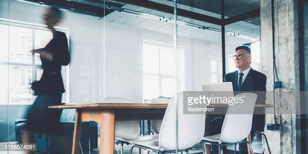 dos personas de negocios en la sala de conferencias - mid adult men fotografías e imágenes de stock