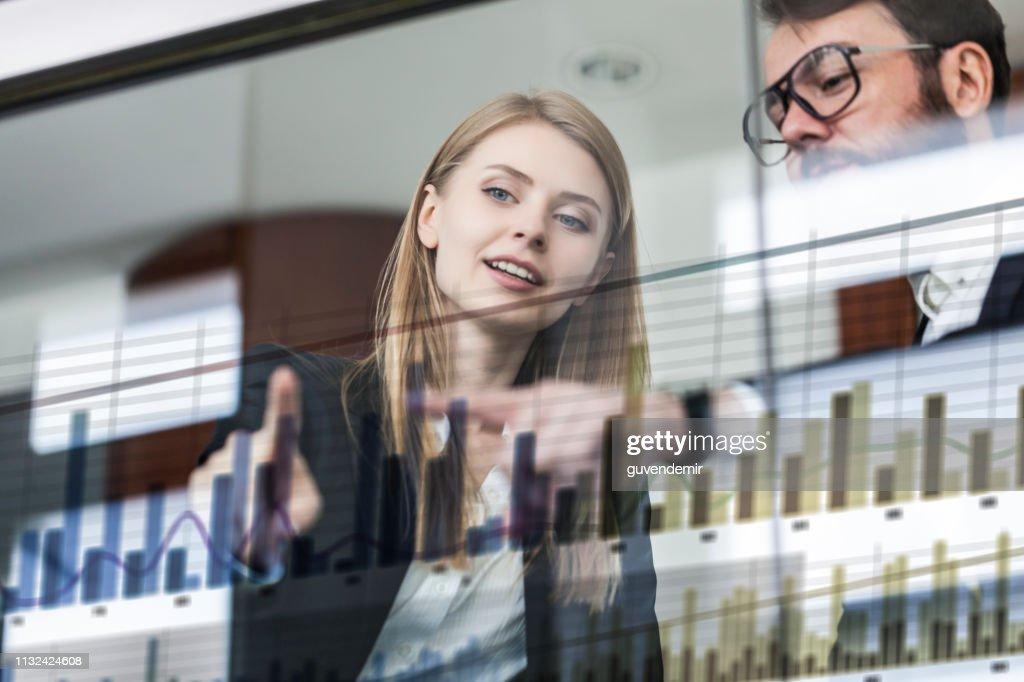Zwei Geschäftsleute vor futuristischem Display diskutieren Finanzgrafik : Stock-Foto