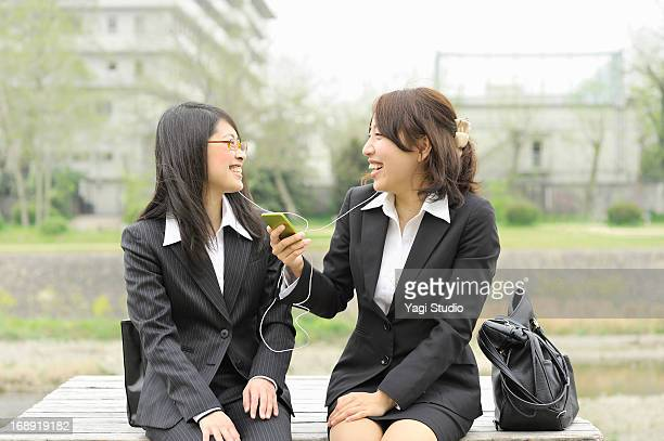 Two Business Woman are relaxing on a bench