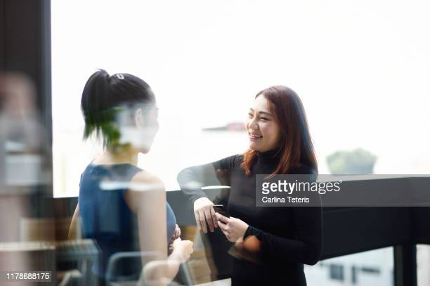 Two business women chatting outside through glass