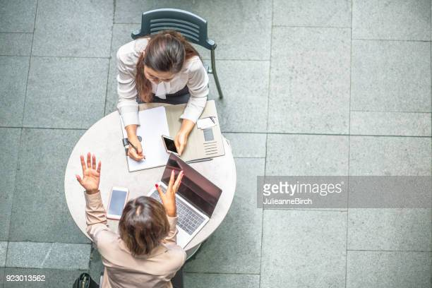Two business women having a meeting at a table outdoors