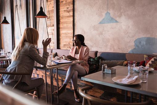 Two business women having coffee break in high-end restaurant 956292330