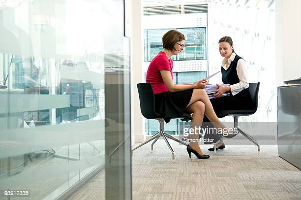 Two business women looking at a file.