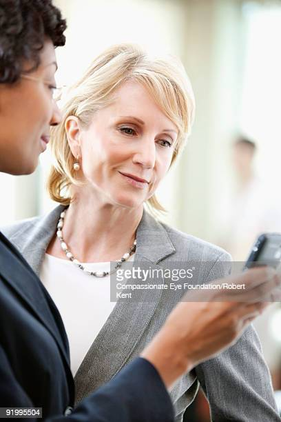 two business women looking at a pda