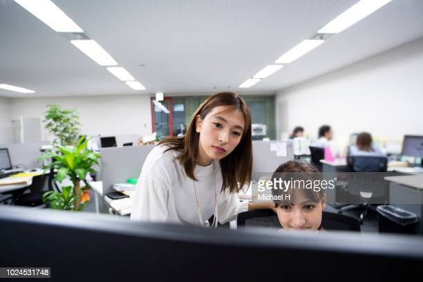 two business women looking at computer at office