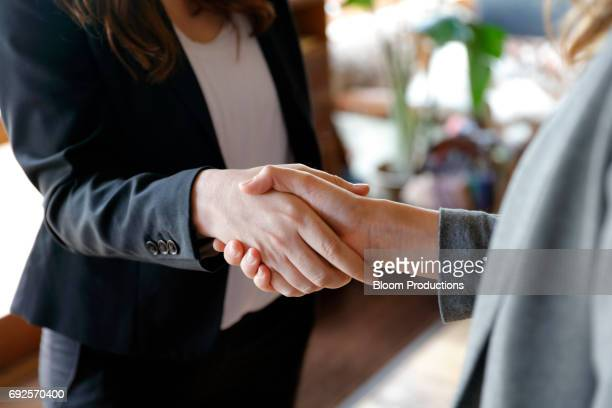two business women shaking hands - agreement stock pictures, royalty-free photos & images