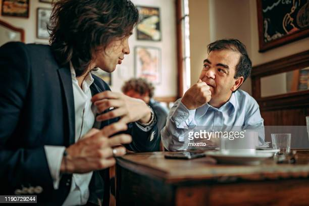 two businessman discussing at cafe - dwarf man stock pictures, royalty-free photos & images