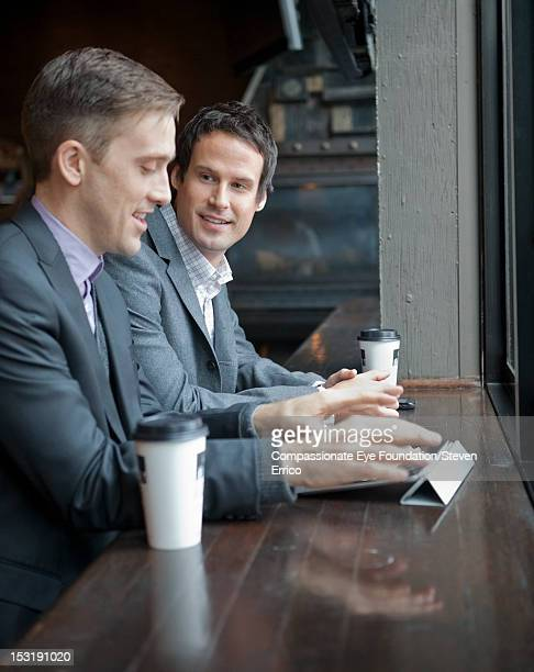 Two businessman drinking coffee in cafe