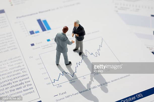 Two businessman figurines atop line graph, elevated view