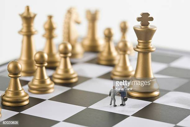 Two businessman figurines shaking hands a top chess board (focus on figurines)
