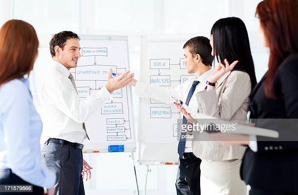two businessman giving presentation using flipchart