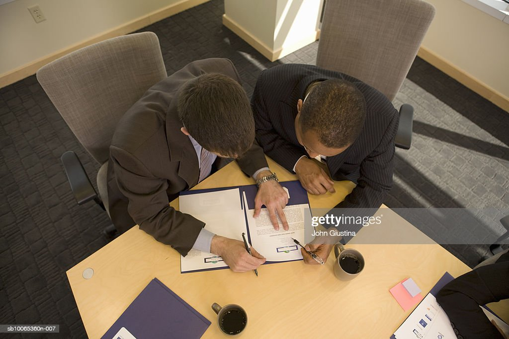 Two businessman looking at documents in conference room, elevated view : Foto stock