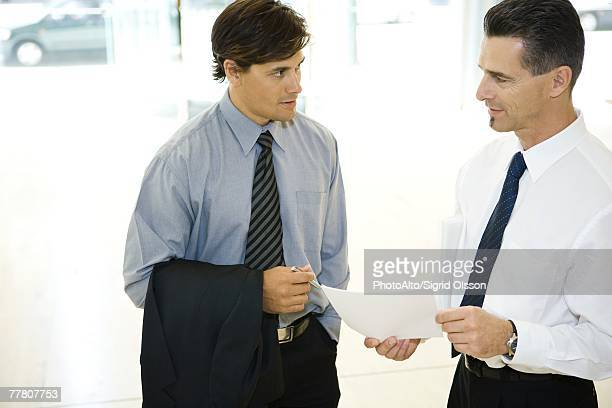 Two businessman looking at each other, discussing, one holding document