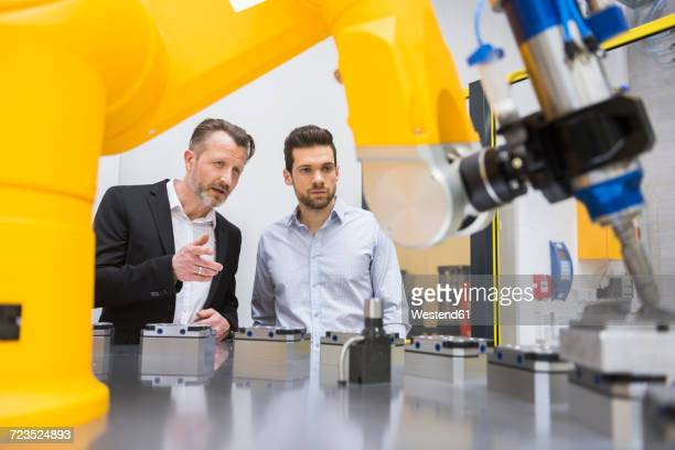 Two businessman observing industrial robots in factory