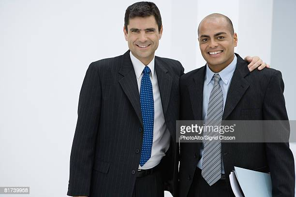 Two businessman, one with arm around the other's shoulder, smiling at camera
