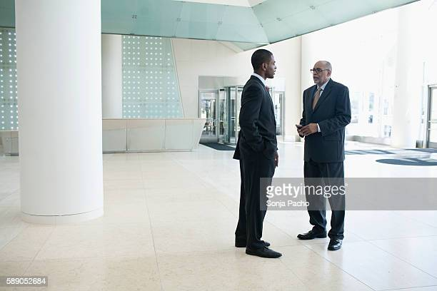 Two businessman talking in lobby of modern building