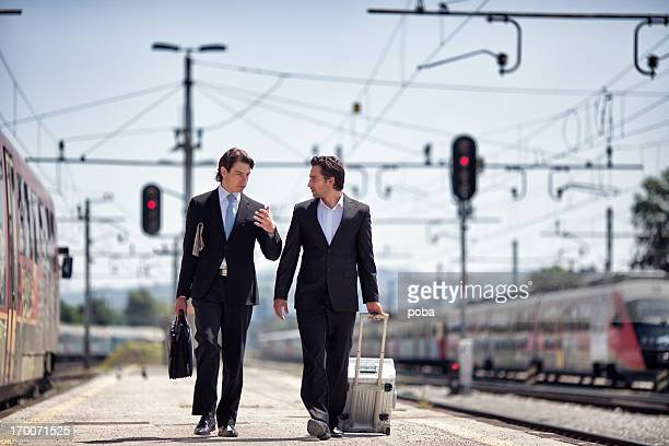 two businessman walking on a train platform.