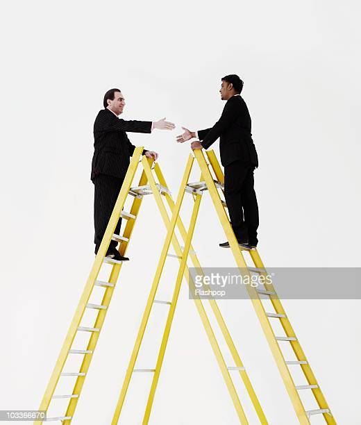 Two businessmen about to shake hands on a ladder