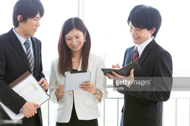 two businessmen and a business woman watching the ipad - somente japonês - fotografias e filmes do acervo
