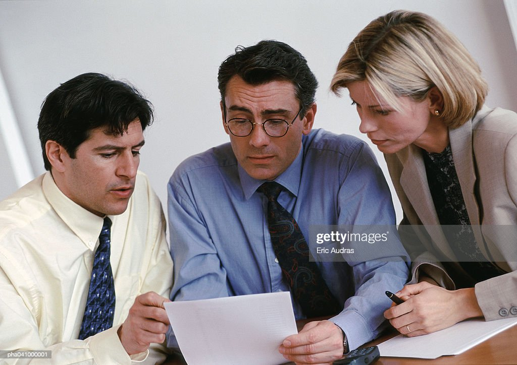 Two businessmen and a businesswoman examining document : Stockfoto