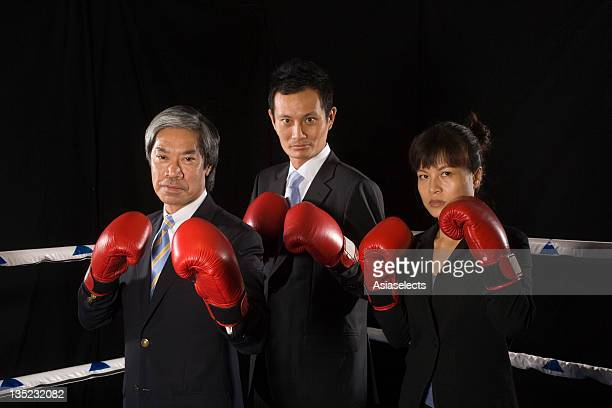 Two businessmen and a businesswoman in a boxing ring