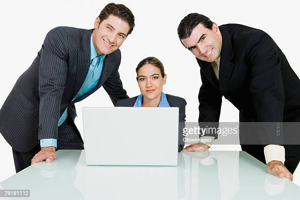 Two businessmen and a businesswoman in a conference room