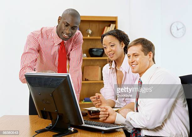 two businessmen and a businesswoman looking at a computer monitor