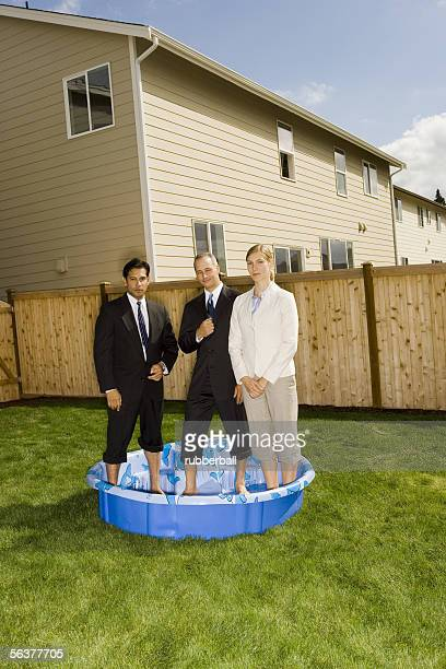 two businessmen and a businesswoman standing in a wading pool - rolled up pants stock pictures, royalty-free photos & images