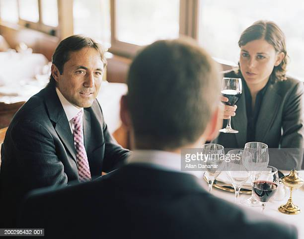 Two businessmen and businesswoman at restaurant table
