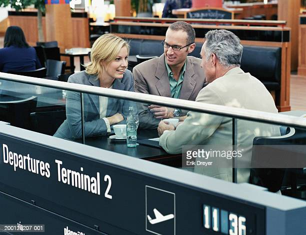 two businessmen and businesswoman in airport cafe - munich airport stock photos and pictures
