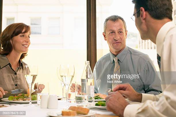 Two businessmen and woman at restaurant table