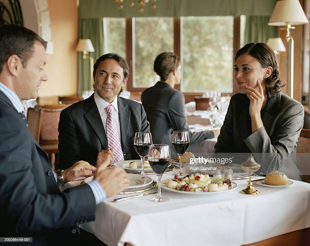 Two businessmen and woman at restaurant table, smiling : Stock Photo