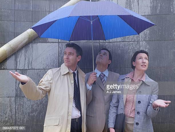 Zwei Geschäftsleute und Frau Zuflucht unter Regenschirm im Regen