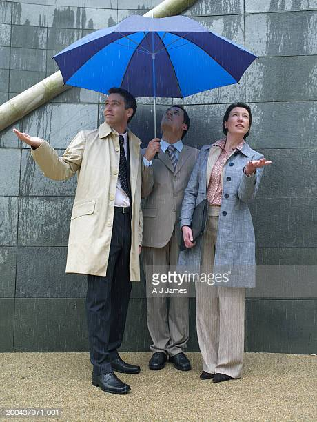 Two businessmen and woman sheltering under umbrella
