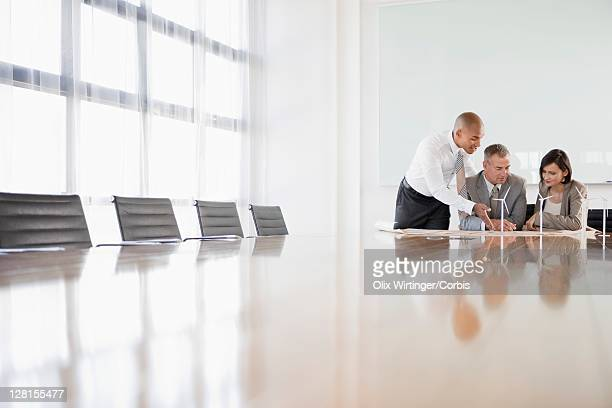 Two businessmen and young woman in conference room