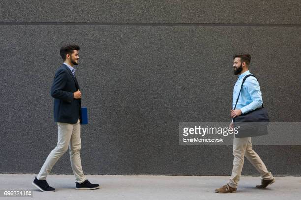 Two businessmen approaching each other