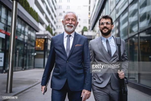deux hommes d'affaires marchent en toute confiance au bureau - plan moyen angle de prise de vue photos et images de collection