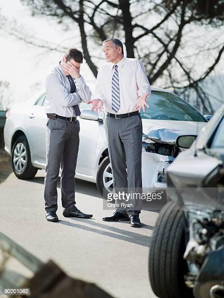 deux hommes d'affaires parler endommagé voitures - accident de la route photos et images de collection
