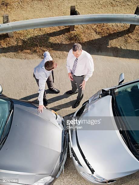 Deux hommes d'affaires parler endommagé voitures