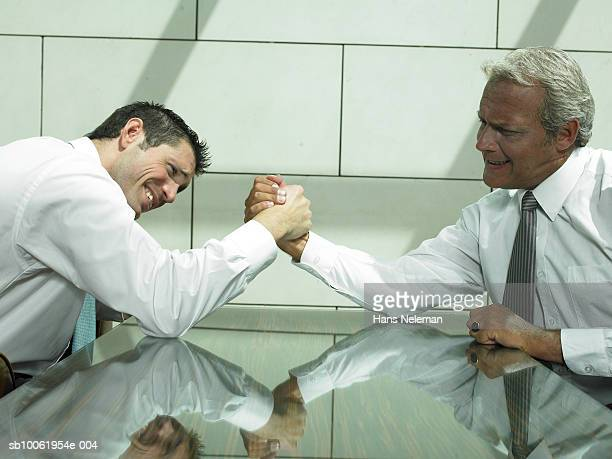 Two businessmen arm wrestling in hotel lobby, side view