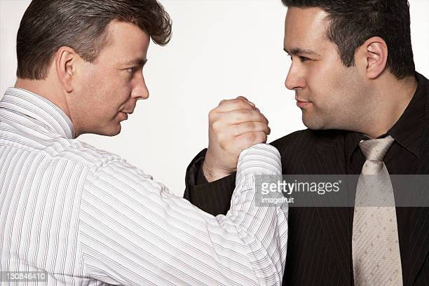 Two businessmen arm wrestling
