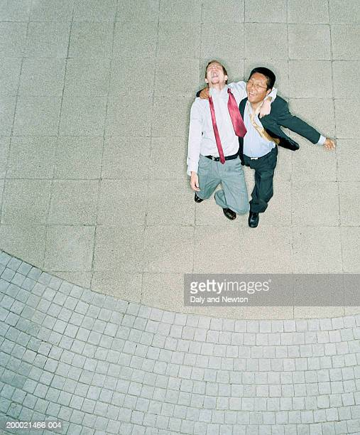 Two businessmen, arms around each other, laughing, elevated view