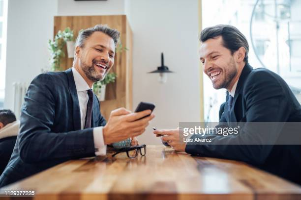 two businessmen at cafe using mobile phone - two people stock-fotos und bilder