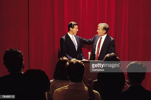 Two businessmen at podium in front of audience