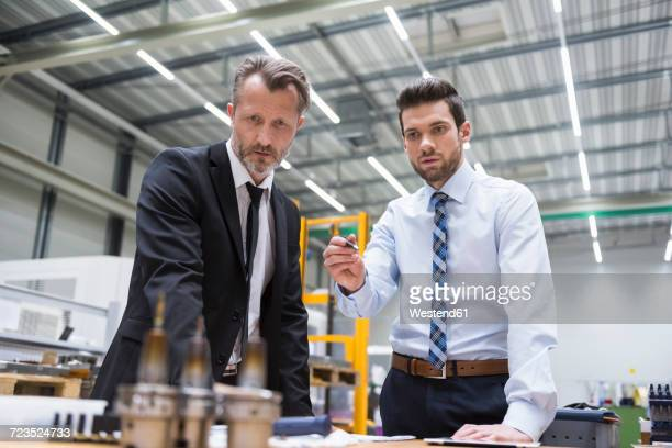 Two businessmen at table in factory shop floor examining product